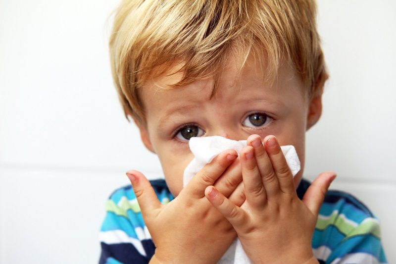 kid blowing nose because of allergies
